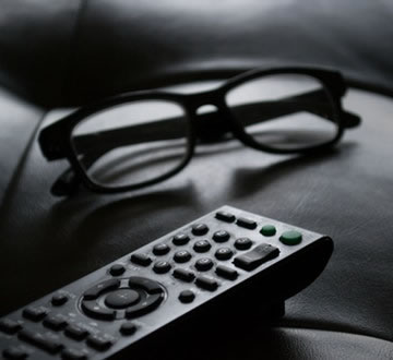 TV remote control on couch next to glasses